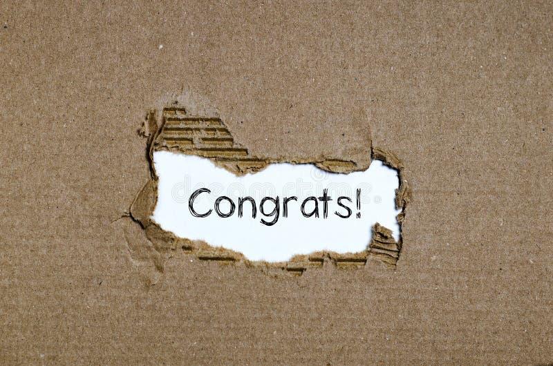 Os congrats da palavra que aparecem atrás do papel rasgado fotografia de stock royalty free