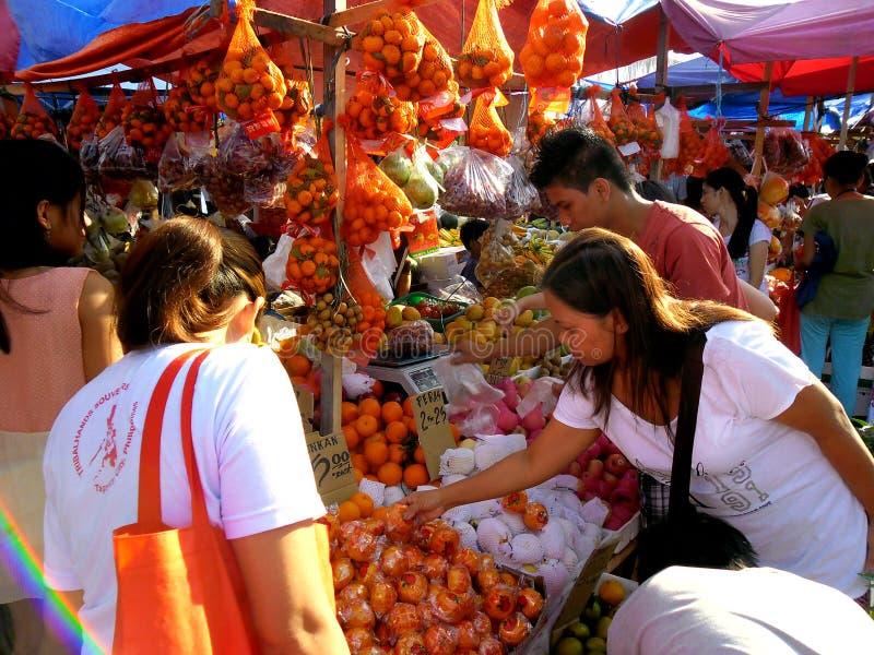 Os consumidores compram de um vendedor do fruto em um mercado em Cainta, Rizal, Filipinas, Ásia imagens de stock