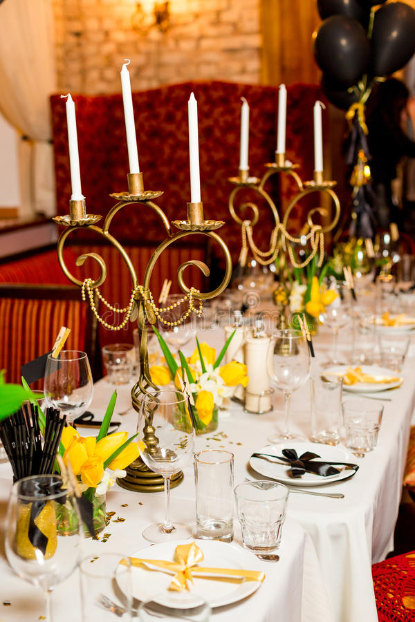 Os convidados do aniversário apresentam o ajuste com as flores frescas no preto e no estilo do ouro, internos fotos de stock