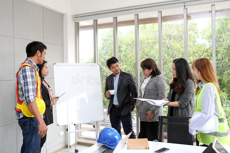 Os coordenadores estão encontrando-se no whiteboard Interior Desi do modelo imagem de stock