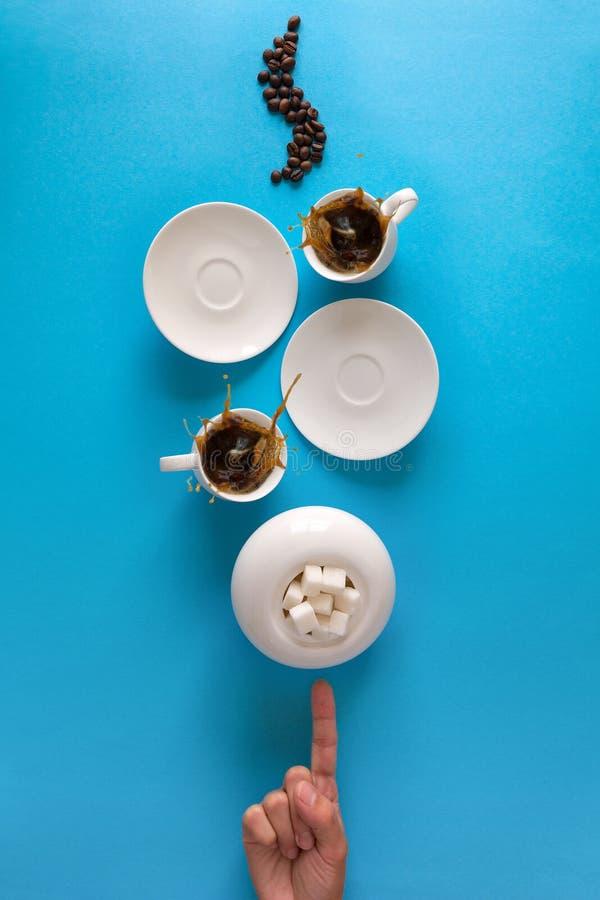 Os copos com café feijões espirram, dos pires, da colher de chá e de café no fundo do papel azul Conceito do bom dia Estilo do al foto de stock