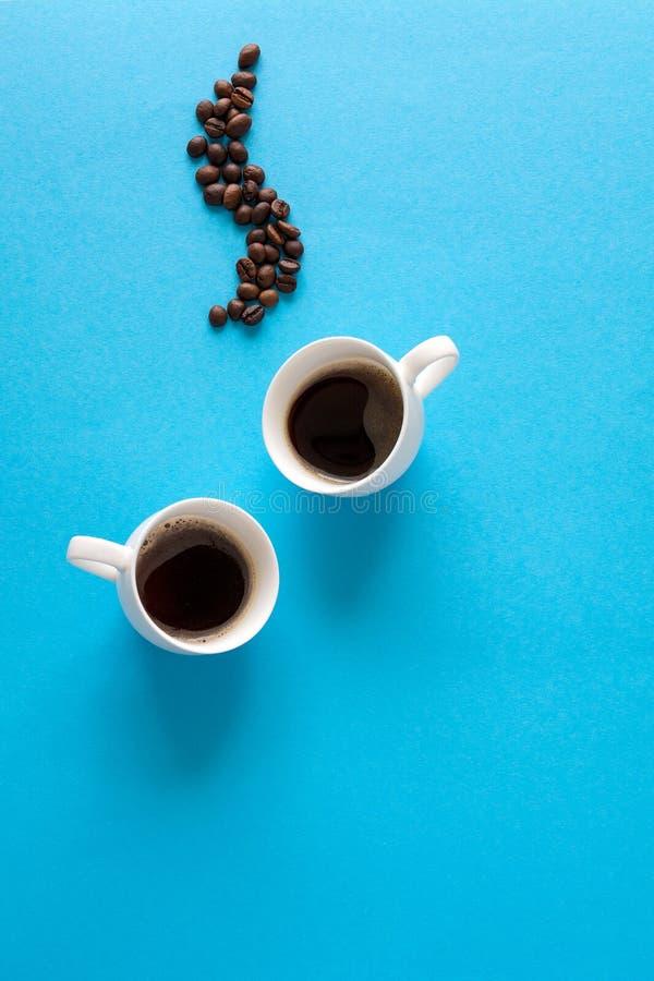 Os copos com café feijões espirram, dos pires, da colher de chá e de café no fundo do papel azul Conceito do bom dia Estilo do al fotos de stock