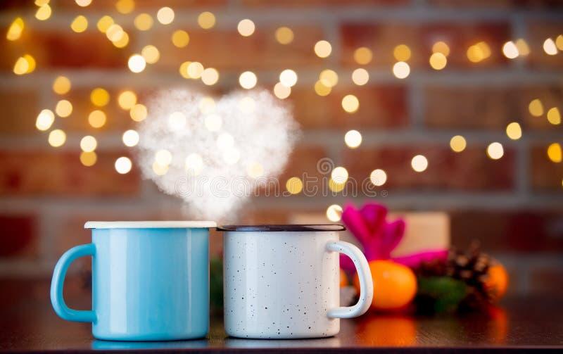 Os copos da bebida quente com forma do coração cozinham foto de stock royalty free