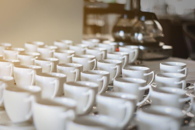 Os copos da sopa e as placas brancas são colocados na tabela para servido fotos de stock royalty free