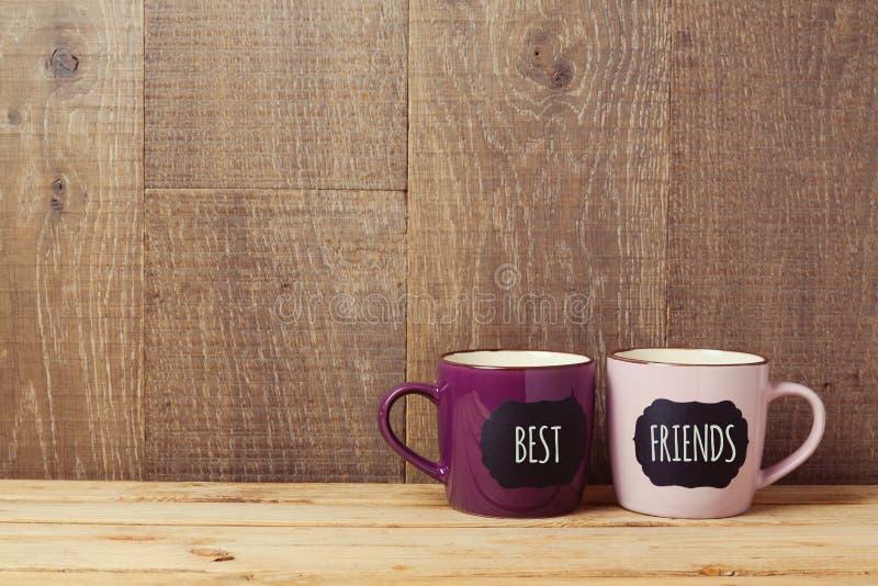 Os copos de café na tabela de madeira com sinal do quadro e os melhores amigos text Celebração do dia da amizade fotografia de stock royalty free