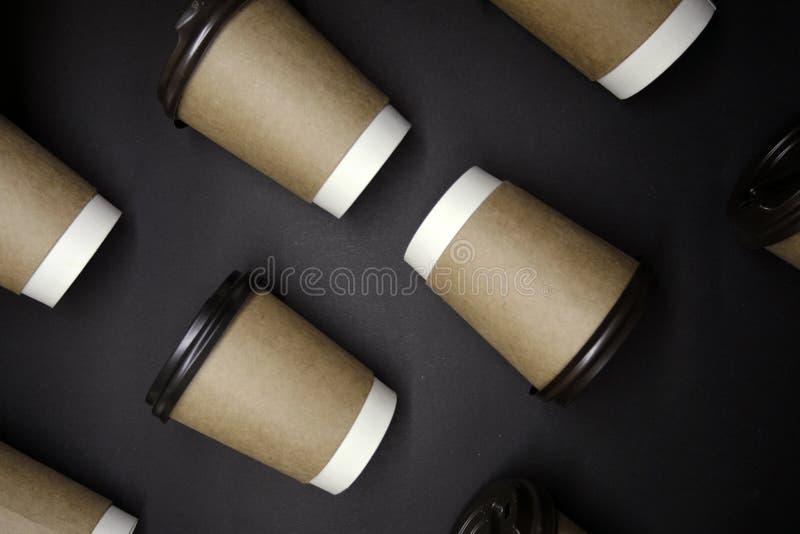 Os copos de papel diagonais colocam no fundo preto foto de stock