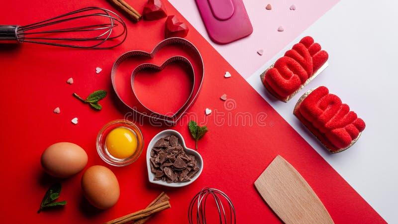 Os corações das bandejas moldam, batem, ovos, espátula de madeira e chocolate raspado Ingredientes a fazer o bolo festivo Bakewar imagem de stock royalty free