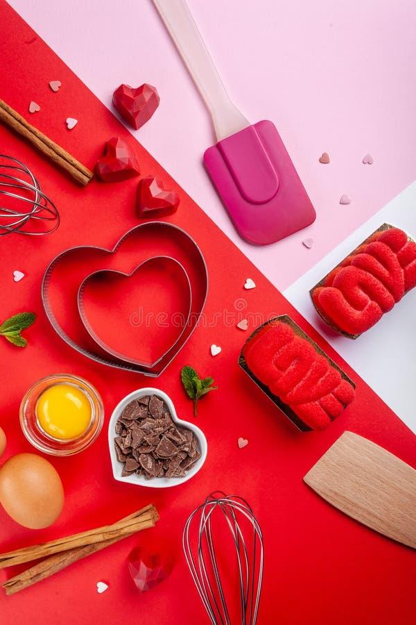 Os corações das bandejas moldam, batem, ovos, espátula de madeira e chocolate raspado Ingredientes a fazer o bolo festivo Bakewar imagens de stock royalty free