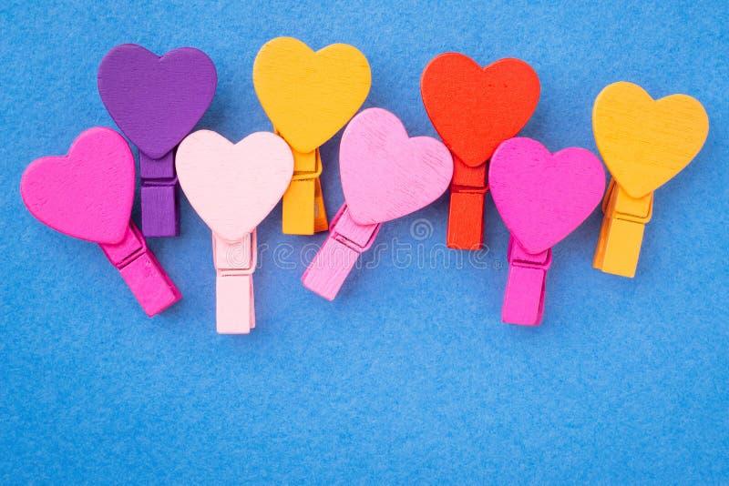 Os corações de madeira coloridos encontram-se de lado a lado em um fundo azul foto de stock royalty free