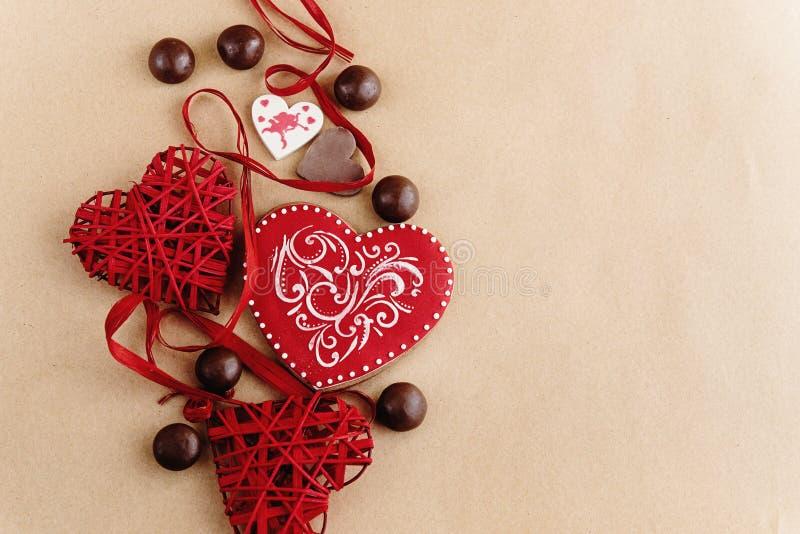 Os corações e as cookies vermelhos à moda originais no fundo do ofício, valen fotos de stock royalty free