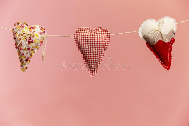 Os corações fizeram do pano em um fundo cor-de-rosa, feito a mão imagens de stock royalty free