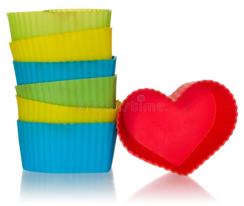 Os corações moldam para cookies em vermelho, amarelo, verde, azul Moldes do silicone arranjados em uma pilha foto de stock