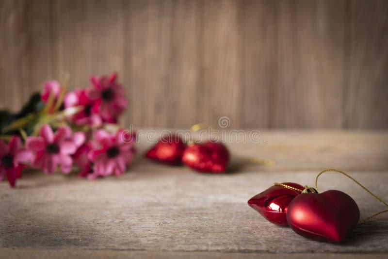 Os corações plásticos vermelhos colocados em uma tabela de madeira lá são uma flor colocada na parte traseira esquerda lá são cor foto de stock royalty free