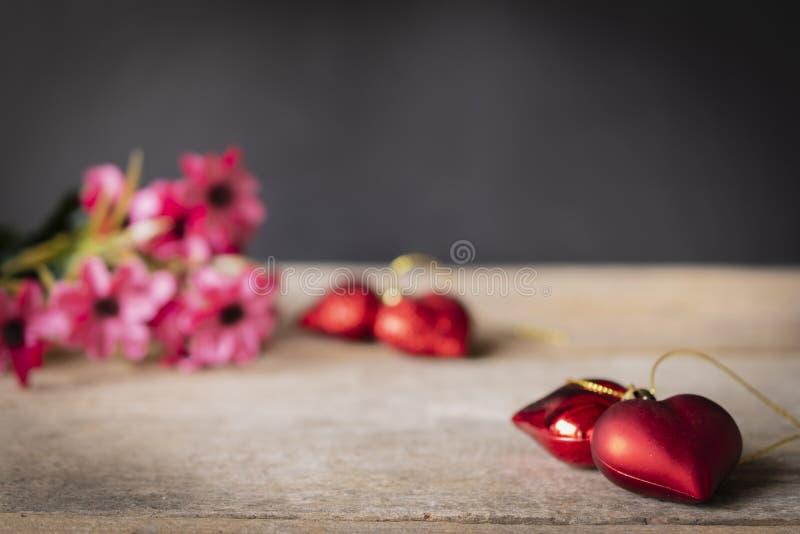 Os corações plásticos vermelhos colocados em uma tabela de madeira lá são uma flor colocada na parte traseira esquerda lá são cor imagens de stock