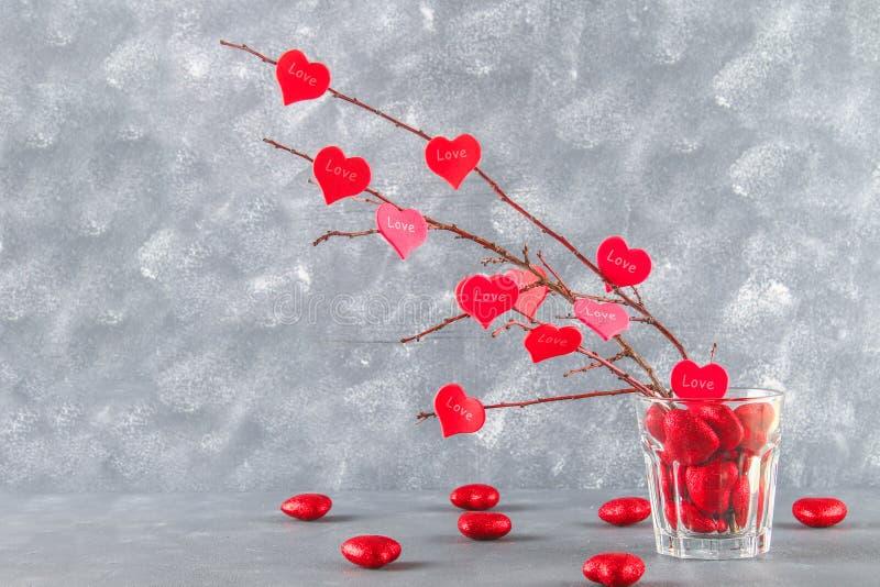 Os corações vermelhos com um amor da inscrição penduram em ramos em um fundo concreto cinzento Árvore de amor O conceito do dia d foto de stock