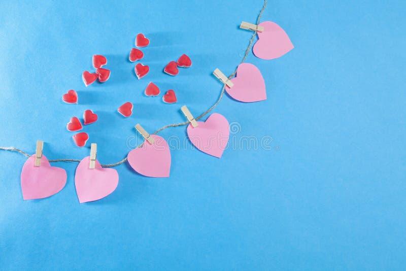 Os corações vermelhos de mastigar o doce de fruta em um fundo azul imagem de stock