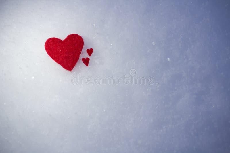 Os corações vermelhos de matéria têxtil encontram-se na neve fria macia fotos de stock