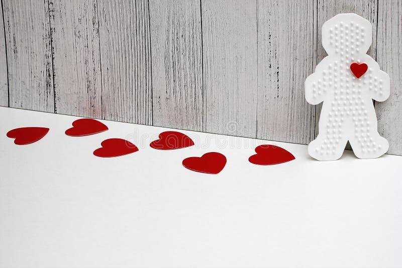 Os corações vermelhos do cartão estão em um fundo branco Figura plástica de um homem com um coração vermelho Conceito do amor Dia imagem de stock