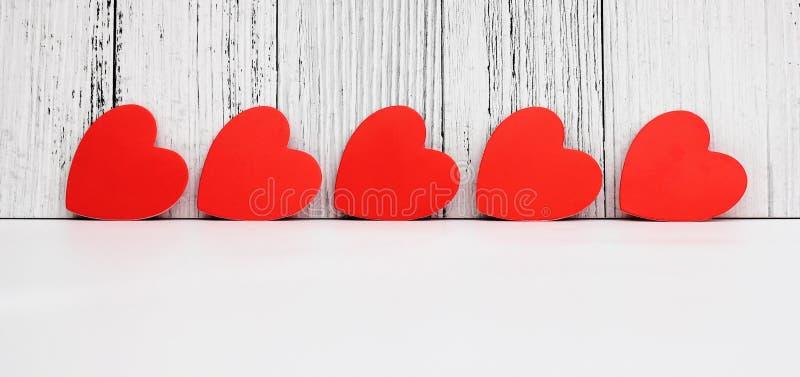 Os corações vermelhos do cartão são arranjados em seguido Projeto e decoração para o dia de Valentim Conceito do amor fotos de stock royalty free