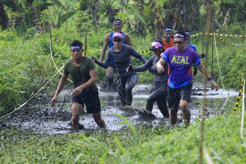 Os corredores cruzam Muddy Track