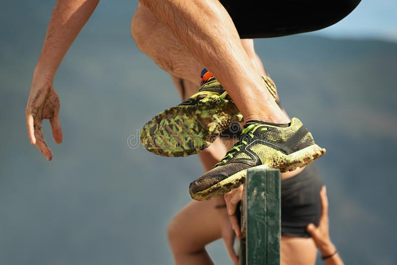 Os corredores de raça da lama, participantes saltam sobre obstáculos fotos de stock royalty free