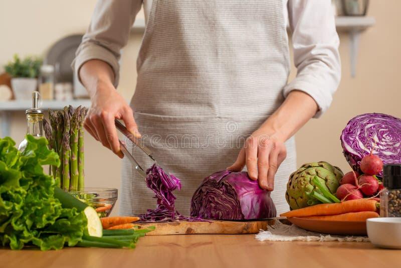 Os cortes do cozinheiro chefe, desbastam a salada roxa fresca da alface O conceito do alimento saudável e integral de perda, desi fotografia de stock royalty free