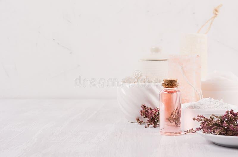 Os cosméticos brancos caseiros orgânicos com flores cor-de-rosa e massagem lubrificam no fundo de madeira branco, beira foto de stock royalty free