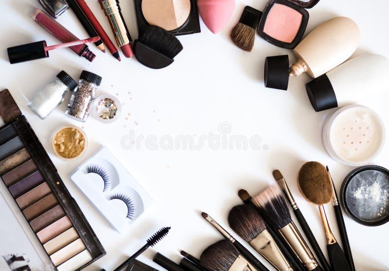 Os cosméticos decorativos para compõem Sombras, escovas e tom de pele Nude na opinião superior do fundo branco foto de stock