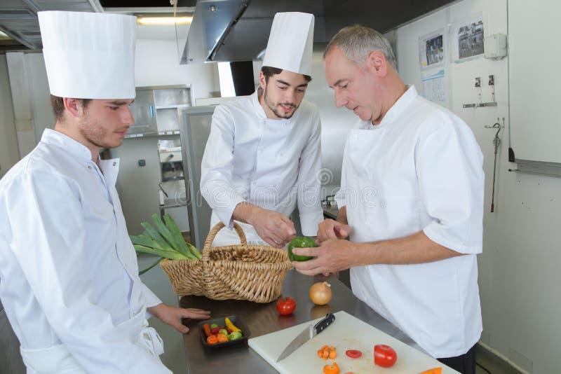 Os cozinheiros chefe profissionais preparam o prato do bife no restaurante fotografia de stock royalty free