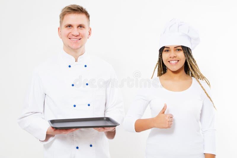 Os cozinheiros da mulher negra de Smule e do homem branco guardam uma bandeja vazia e mostram-na como foto de stock