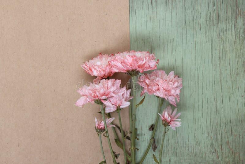 Os cravos-da-índia cor-de-rosa florescem no papel do ofício e no fundo de madeira do verde Fundo floral com copyspace fotos de stock royalty free