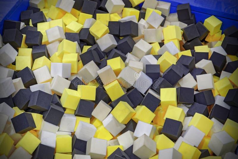 Os cubos coloridos da borracha de espuma no trampolim pit o fundo do close-up imagens de stock