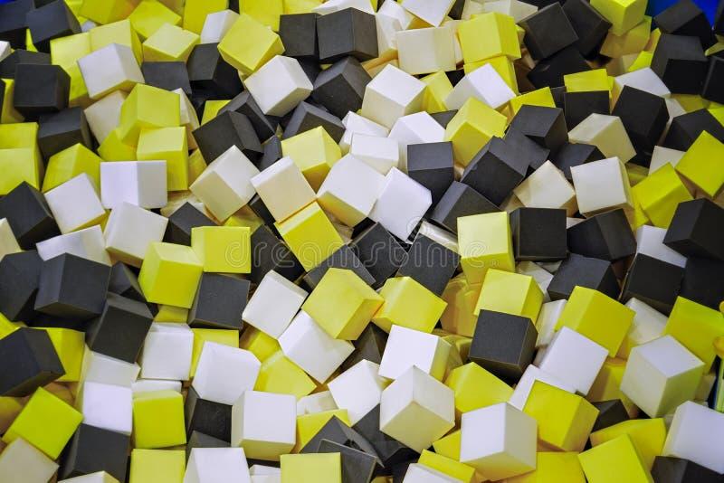 Os cubos coloridos da borracha de espuma no trampolim pit o fundo do close-up foto de stock