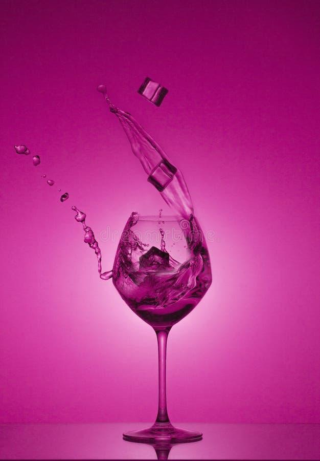 Os cubos de gelo caem em um vidro e a água é derramada para fora Água que espirra fora de um vidro de vinho alto imagem de stock royalty free