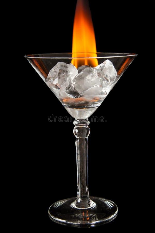 Os cubos de gelo no vidro com a chama no preto brilhante surgem foto de stock royalty free