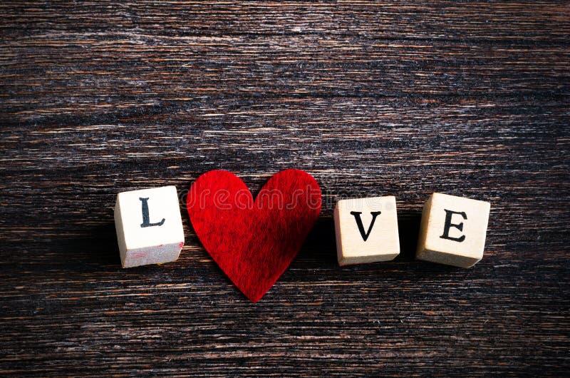 Os cubos de madeira com inscrição amam o e o coração vermelho de matéria têxtil no fundo de madeira Espaço livre para seu texto fotos de stock