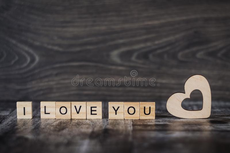 Os cubos de madeira da frase eu te amo e um coração de madeira em uma obscuridade foto de stock royalty free