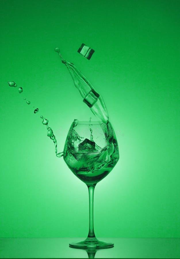 Os cubos do Ce caem em um vidro e a água é derramada para fora Água que espirra fora de um vidro de vinho alto fotografia de stock royalty free