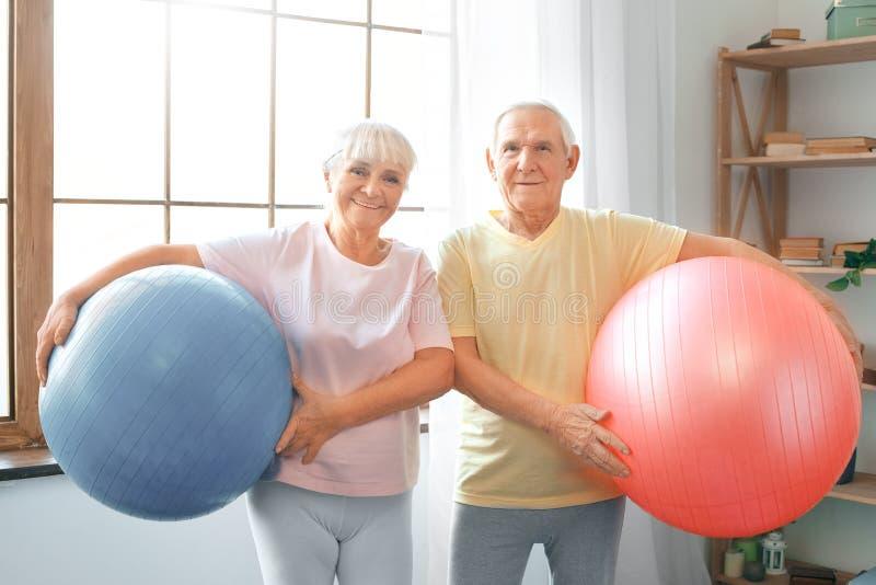 Os cuidados médicos superiores do exercício dos pares junto em casa levam as bolas que olham a câmera fotos de stock royalty free