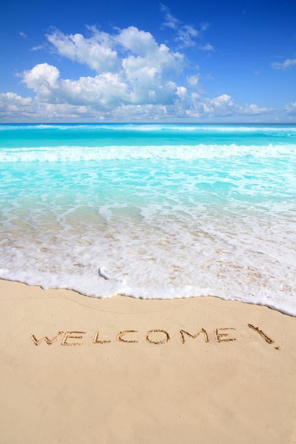 Os cumprimentos dão boas-vindas ao encanto da praia escrito na areia fotos de stock