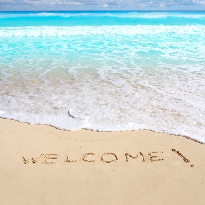 Os cumprimentos dão boas-vindas ao encanto da praia escrito na areia foto de stock