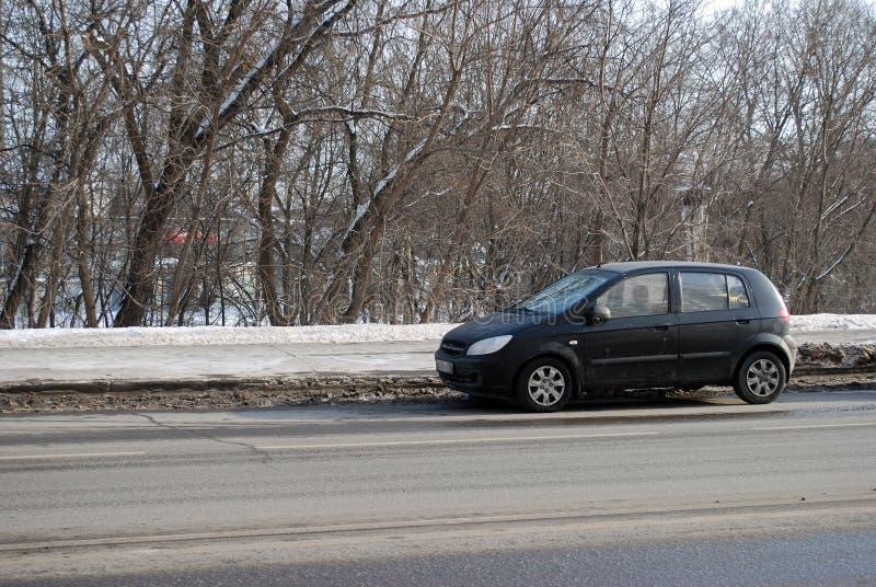 Os custos pretos do carro de Getz Hyundai estacionados na estrada na tarde do inverno fotos de stock