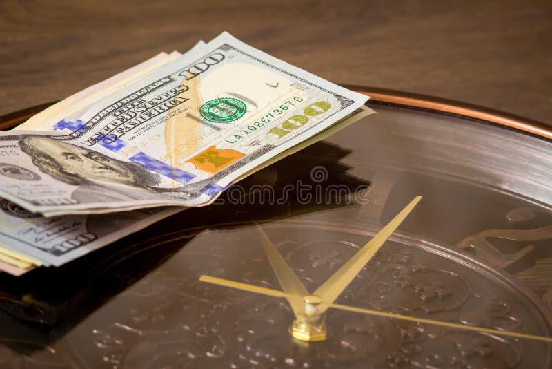Os dólares americanos encontram-se no pulso de disparo grande Hora de ganhar o dinheiro O tempo é money_ foto de stock