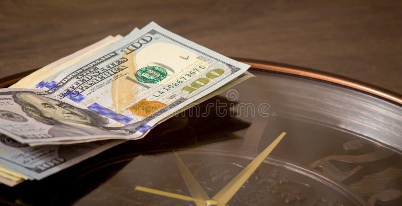 Os dólares americanos encontram-se no pulso de disparo grande Hora de ganhar o dinheiro O tempo é money_ fotos de stock royalty free