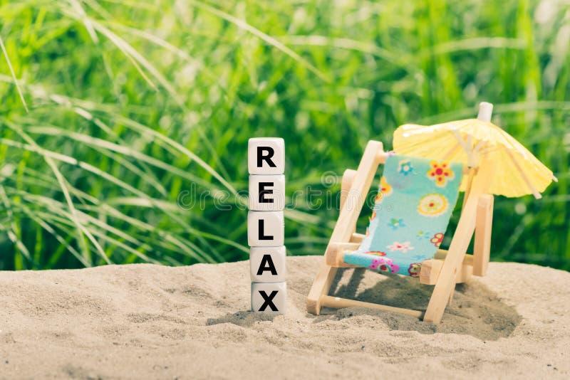 Os dados colocaram ao lado de um formulário que da cadeira de praia a palavra 'relaxa ' imagem de stock