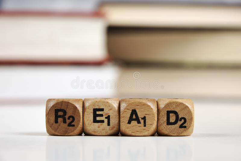 Os dados de madeira com as palavras leram com livros borrados fotos de stock