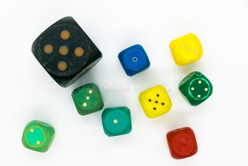 Os dados plásticos do jogo das cores muito velhas e várias no fundo branco surgem imagem de stock royalty free