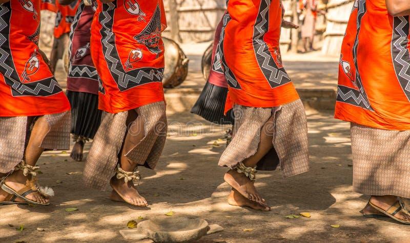 Os dançarinos africanos tradicionais em sandálias dançam fora na roupa brilhantemente colorida foto de stock