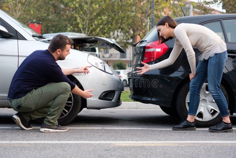 Os danos de exame do corpo de carro dos povos após a batida do carro imagem de stock royalty free