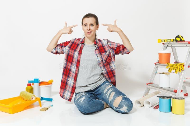 Os dedos cansados do ponto da mulher a dirigir como se se dispara n, sentam-se com os instrumentos para a renovação isolados no b imagens de stock